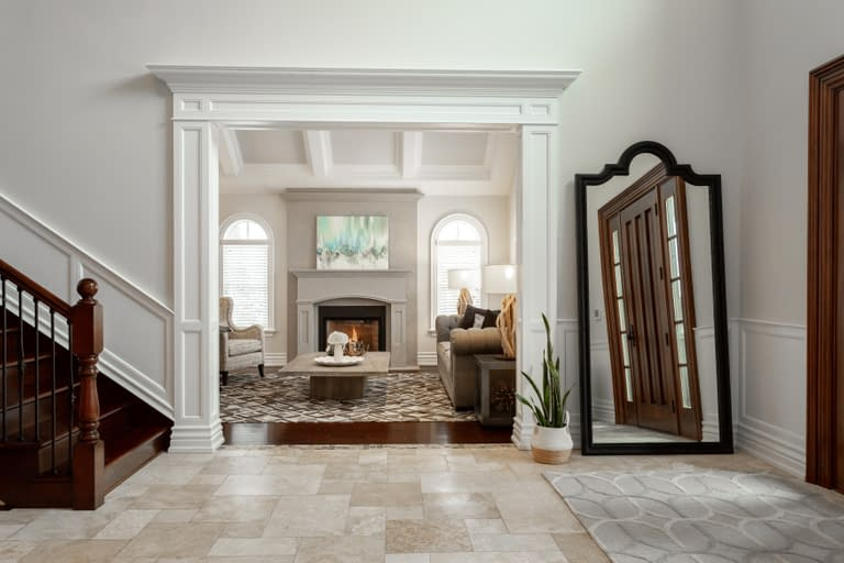 luxury foyer with corridor going into a living room with fireplace and cozy living area