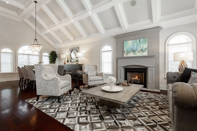 Real Estate Photography of a luxury living room with tall vaulted ceiling and warm fire place